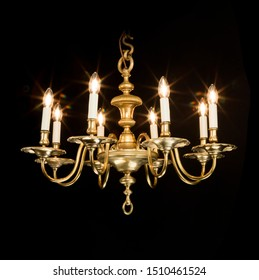 Lovely brass chandelier wires with bulbs on and lit isolated on black