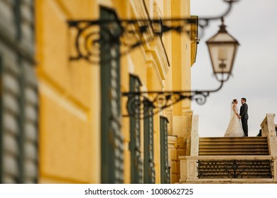 Lovely bride and groom posing on steps near old yellow structure