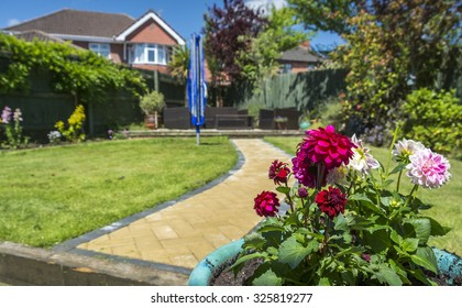 Lovely, British garden in the summer, showing red and pink flowers, and a yellow garden path