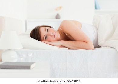 Lovely brunette female thinking while lying on a bed
