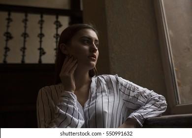Lovely brunette model posing near the window at the room