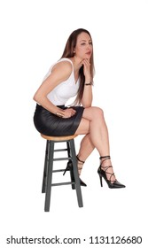A lovely brunette young woman sitting in a black leather skirt on a