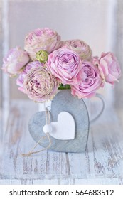 Lovely bunch of flowers .Close-up floral composition with a pink roses .Many beautiful fresh pink roses on a table. Congratulation with a flowers in a pot decorated with a heart.