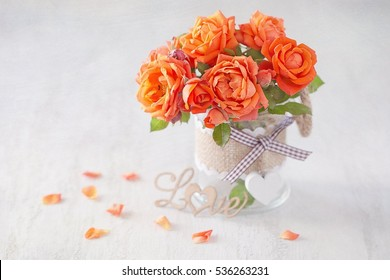 Lovely bunch of orange flowers .Beautiful fresh roses flowers in a vase decorated with a heart on a background with texture .Happy Valentine's Day!