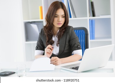 Lovely businesswoman taking a look at digital data displayed on the laptop screen