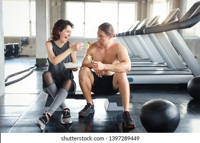 lovely caucasian couple fitness man and woman take a rest and eating salad in gym after finish fitness training with happy smiling face