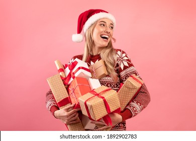 Lovely Caucasian woman in Xmas outfit holding stack of wrapped Christmas gifts on pink studio background. Pretty millennial lady shopping for festive season. Holiday sale concept