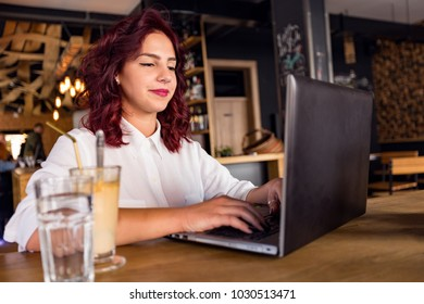 Lovely charming young woman relaxing and having a coffee while using her laptop.Student concept