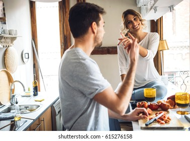 Lovely cheerful couple cooking dinner together and having fun at modern kitchen.