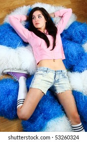 Lovely cheerleader wearing pink sweater and jeans shorts relaxing on the pom-poms.