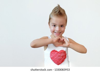 Lovely child boy smiling shows heart sign. Portrait kid blond 6 year with smile making hands gesture love. Studio isolated white background.