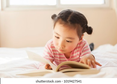 A lovely child reading in bed