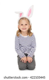 Lovely child. Shot of a beautiful little girl wearing bunny ears sitting at the studio looking to the camera smiling isolated on white.