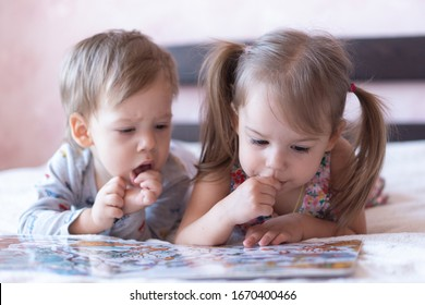 Lovely children - brother and sister, reading a book, on the bed