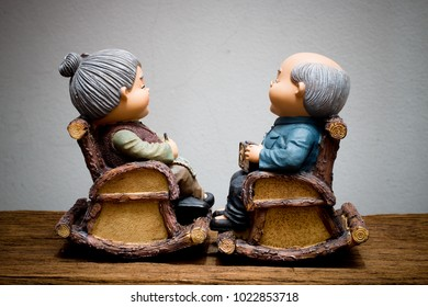 lovely chinese grandparent doll, grandfather doll holing radio and grandmom is knitting crochet, siting rocking bamboo chair on wooden table with gray concrete wall. Chinese New Year & Love concept.