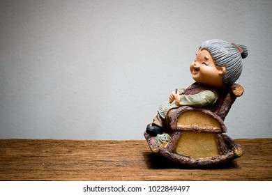 lovely chinese grandparent doll, grandmom is knitting crochet, siting rocking bamboo chair on wooden table with gray concrete wall. Chinese New Year & Love concept.