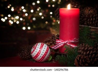 Lovely Christmas Still Life of a Lit Red Candle with an Ornament and Pine Cones with a Christmas Tree in the Background and Room for your Words or Text.