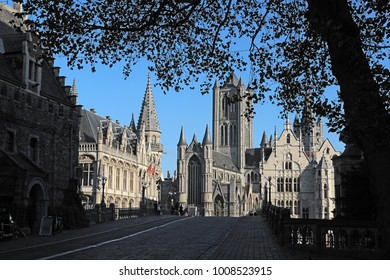 The lovely city of Ghent, Belgium, seen from the shadows across the cobble stoned Sint Michiels bridge. The three towers of the medieval churches of the city centre rise through the leaves of a tree.