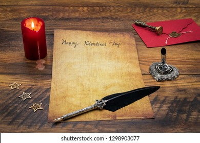 Lovely classic Valentine's Day cad, hand written with ink and quill on vintage paper, red envelope with wax seal, lit candle, wood decorations, silver quill stand on antique oak – front view