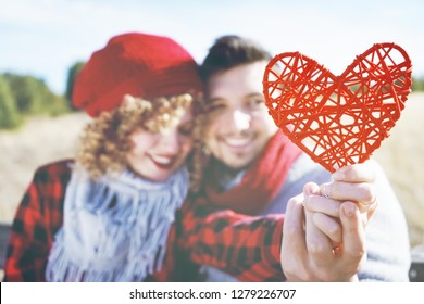 Lovely close-up of a beautiful red heart held by a romantic young couple in love in a nice bokeh as background outdoor. It reminds love or health care