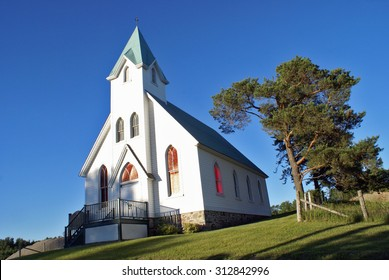 A lovely composition of a white church in the charming countryside.