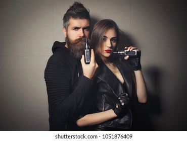 Lovely couple of bearded strong man and pretty sexy cute woman smoking electronic cigarettes vape. Couple in love, brutal handsome hipster man with long beard and amazing beauty girl, wonderful eyes.