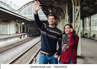 Lovely couple being on platform of railway station, wave someone as look into distance, meet their relatives or friends. Young married woman and man say goodbye someone. Farewell concept.