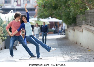 Lovely couple dancing West Coast Swing in the streets, carefree and happy.