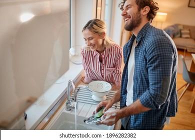 Hermosa pareja que prepara los platos juntos en la cocina