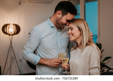 Lovely couple drinking wine while hugging in their living room.