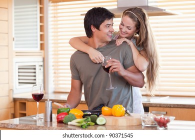Lovely couple drinking wine while hugging in their kitchen