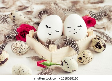Lovely couple of easter eggs with drawn faces closed eyes dreaming nesting in box decored with roses and quail feathers.