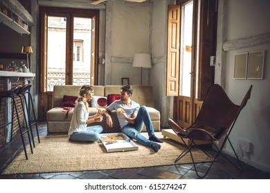 Lovely couple eating pizza while sitting on floor of living room in modern apartment.