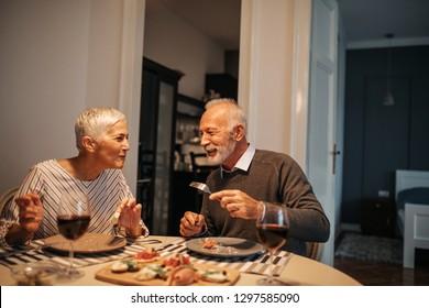 Lovely couple enjoying dinner at home