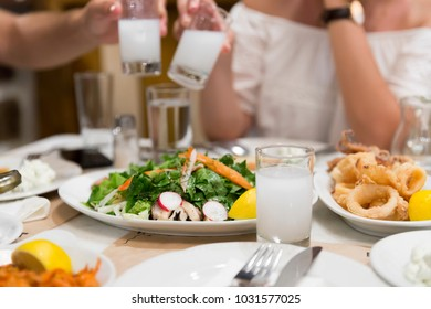 Lovely Couple or Friends Sitting, Drinking, Say Cheers and drinking Turkish Traditional Drink Raki. Ouzo is a dry anise flavoured aperitif that is widely consumed in Greece, Cyprus and Lebanon.