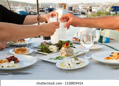 Lovely Couple or Friends Sitting, Drinking, Say Cheers and drinking Turkish Traditional Drink Raki. Ouzo is a dry anise flavoured aperitif that is widely consumed in Greece, Turkey, Cyprus and Lebanon