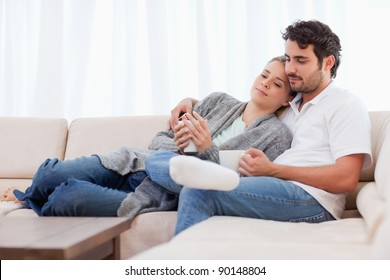 Lovely couple having a cup of coffee in their living room