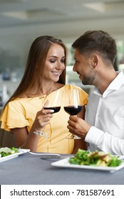Lovely Couple Having Dinner In Luxury Restaurant. Young Handsome Man And Beautiful Woman Drinking Red Wine Eating Salad. Romantic Relationship. High Quality Image.