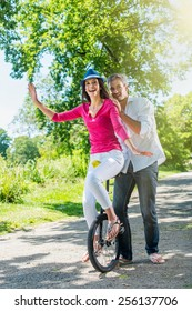 A lovely couple is having fun on a unicycle in the park. A beautiful woman is trying to ride the unicycle, while her grey hair boyfriend is holding her. They are wearing casual clothes.