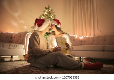 Lovely couple kissing while opening Christmas gifts