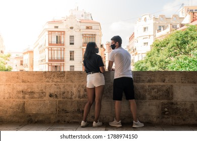 Lovely couple looking to each other wearing facial mask to prevent coronavirus, on a sunny day at a historic building of Valencia center. Concept of sightseeing during covid in Spain.