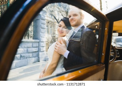 The lovely couple in love embracing near car