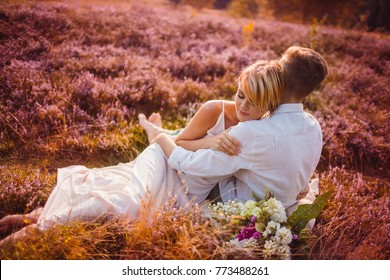 The lovely couple in love embracing and sitting  on the grass