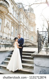 The lovely couple in love embracing and standing on the stairs