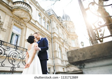 The lovely couple in love embracing and standing near building