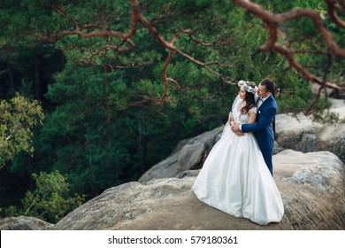 The lovely couple in love embracing and standing on the stones