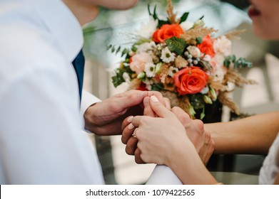 The lovely couple in love hold of hands. Stylish wedding bouquet of flowers.