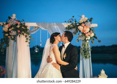 The lovely couple in love standing  and kissing  near wedding archway