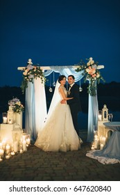 The lovely couple in love standing    near wedding archway