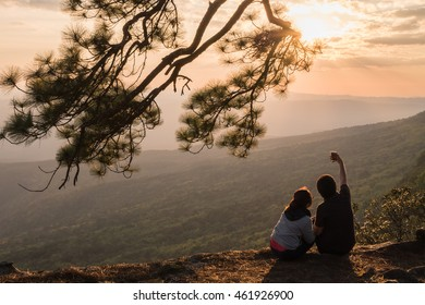 Lovely couple making selfie by use smartphone camera during sunset time at Phu Kradueng National Park,Thailand